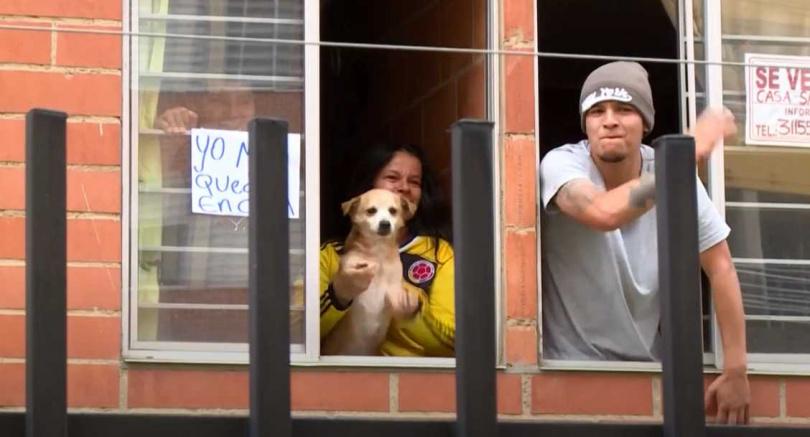 波哥大居民一家大小連寵物都靠在窗邊和員警一起熱舞。(圖/AFP)