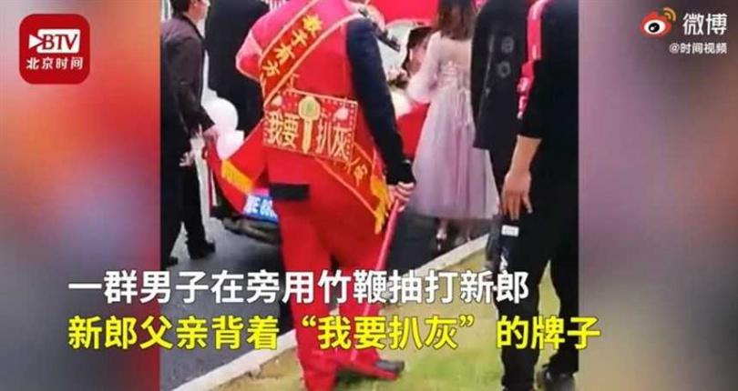 新郎父親身上掛著「我要扒灰」的牌子。(圖/翻攝自時間視頻微博)