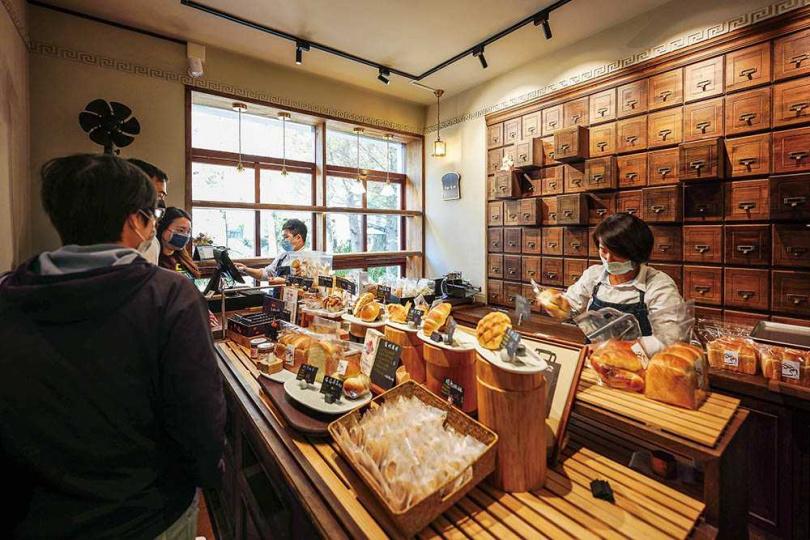 以復古藥櫃做裝飾與木架擺放麵包,帶出符合老宅的溫馨感。(圖/焦正德攝)