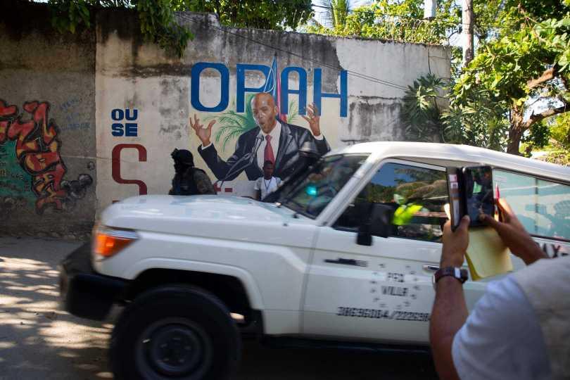 一輛載有海地總統摩依士(Jovenel Moïse)遺體的救護車駛過領導人官邸附近的一幅壁畫。(圖/達志/美聯社)