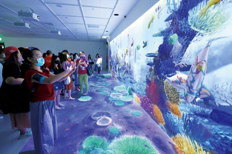 來到「虛實互動」區,遊客可在現場的平板電腦上,透過益智遊戲與彩繪軟體,組合出海洋生物,並投射到牆上的虛擬海洋中。(圖/于魯光攝)