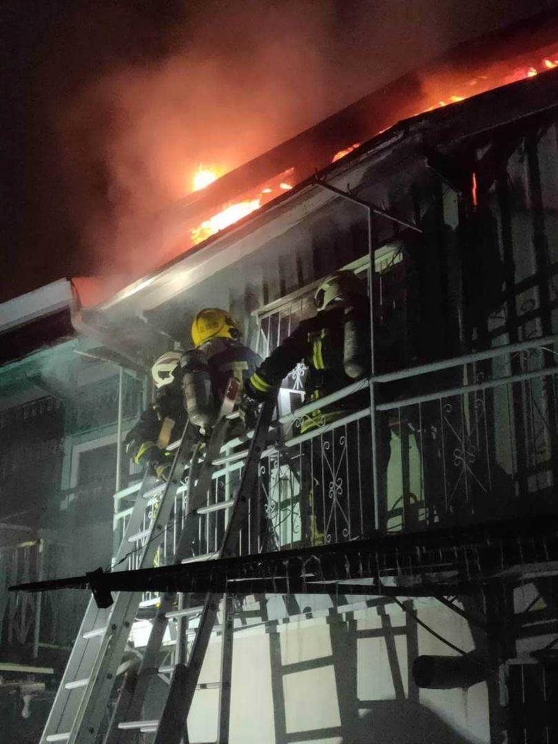 嘉義市南田公園附近凌晨大火,消防人員架梯搶救。(圖/讀者提供)