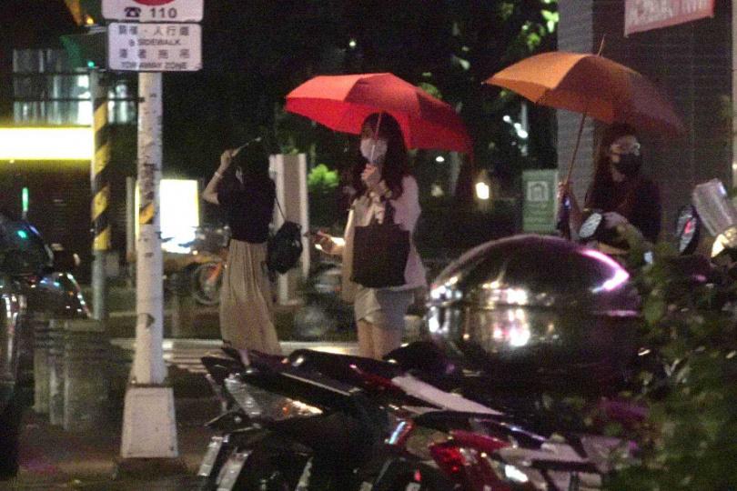 貝貝蕾(左)、潘映竹(中)、蘿莉塔(右)三人結束直播活動後一起離開,貝貝蕾還拿起護目面罩充當雨傘。(圖/攝影組)