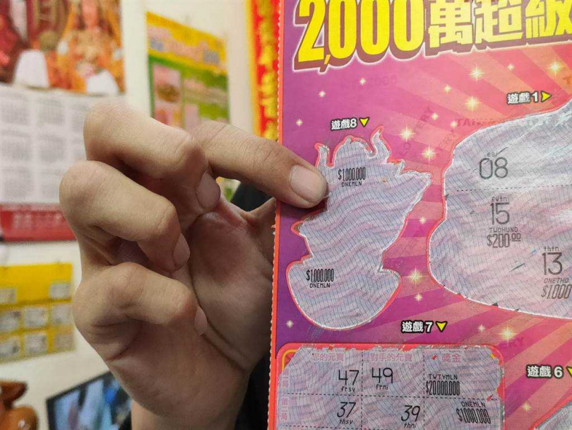 賴國隆開心拿出中獎彩券,表示一開始以為是10萬,大家一起對發現有6個零,當場尖叫。(圖/中國時報吳建輝攝)