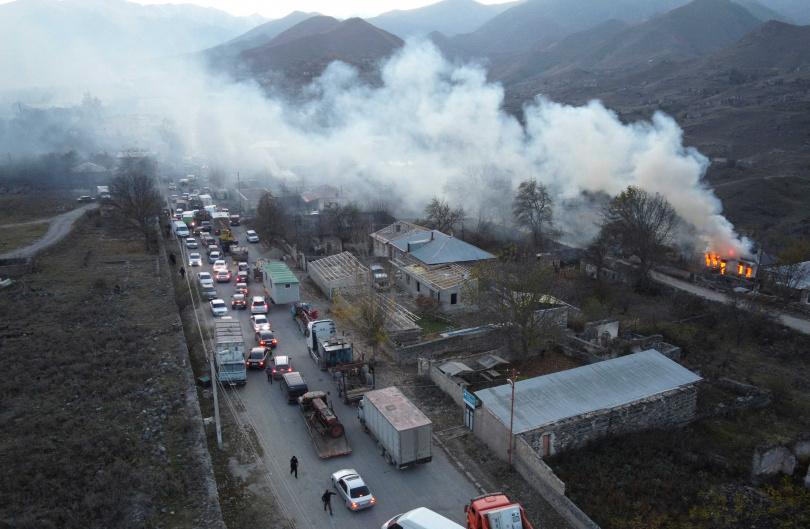 焚燒的家園與離去的民眾,形成鮮明的對比。(圖/達志/美聯社)