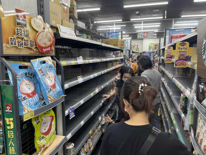 台北、新北市疫情警戒升至三級,大量民眾衝入超商,搶購罐頭、泡麵等物資,賣場人員緊急補貨。(圖/中國時報蔡雯如攝)