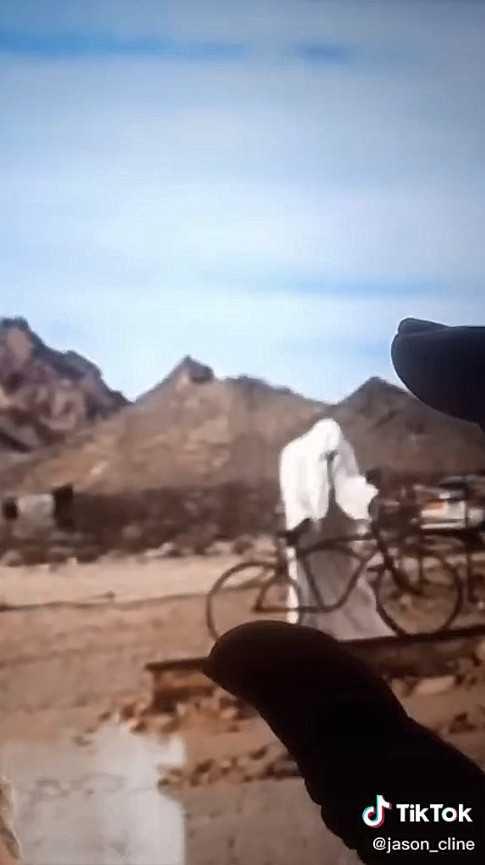 一名身穿白色斗篷的人,站在自行車前。(圖/翻攝自Jason Cline抖音)