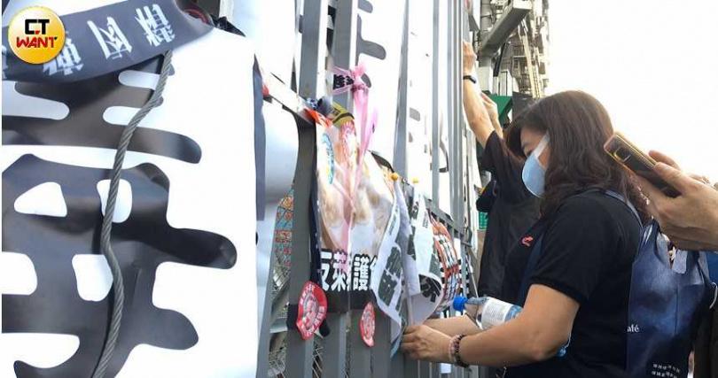 民眾將抗議標語,貼在民進黨中央前的鐵拒馬上。(圖/黃耀徵攝)