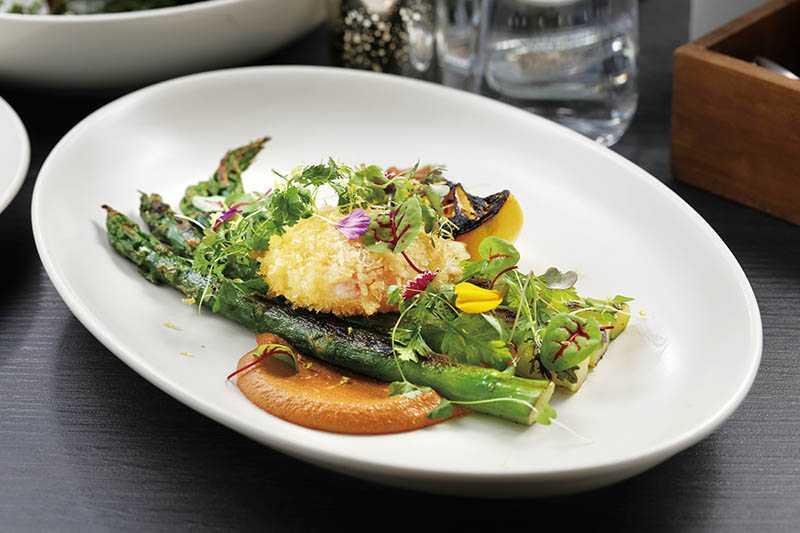 「炙烤綠蘆筍」是炙烤後的綠蘆筍,加上低溫烹調半熟香脆蛋及甜椒堅果醬、香草,口感清爽溫潤。(420元)(圖/于魯光)