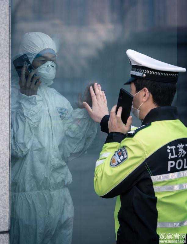 醫警夫妻隔著玻璃打電話,伸手卻碰不到對方。(圖/翻攝自觀察者)