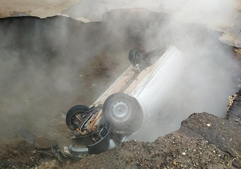俄羅斯南部一處停車場,因地下熱水管線爆裂,地面被炸出一個洞,一輛車當場掉進坑裡,車上2名男子被流出的熱水燙死。(圖/翻攝網路)