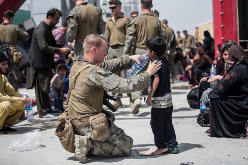 士兵餵小朋友喝水。(圖/翻攝自臉書/U.S. Marine Corps)