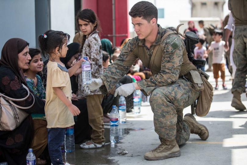 士兵遞水給小朋友。(圖/翻攝自臉書/U.S. Marine Corps)