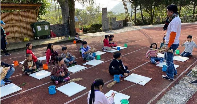 用心快樂去年邀請藝術家阿信.沙華克一同到新竹縣尖石國小,教學童利用顏料和花、草等媒材,在操場席地作畫,孩子們都十分投入。(圖/讀者提供)