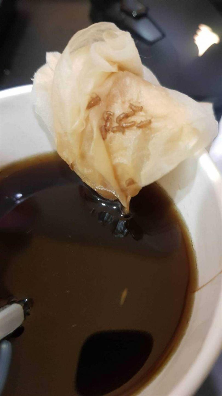 網友買咖啡喝第一口就驚覺口感有異,沒想到伸手一撈竟撈出數粒蟑螂蛋。(圖/翻攝PTT)