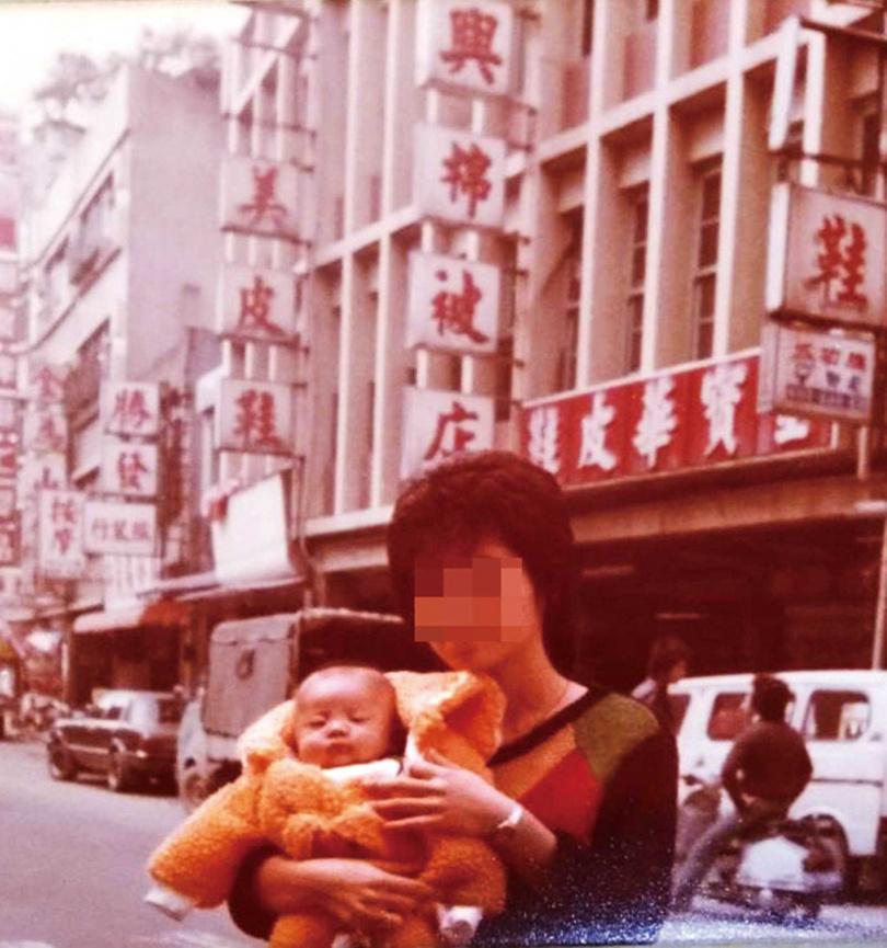 早期陳家從事棉被買賣,圖為陳媽媽懷抱著陳泰源在饒河街《隆興棉被店》2號店前合影。(圖/讀者提供)