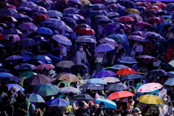 水柱含有刺激皮膚的成分,迫使部分抗議人士打開大傘抵擋。(圖/路透社)