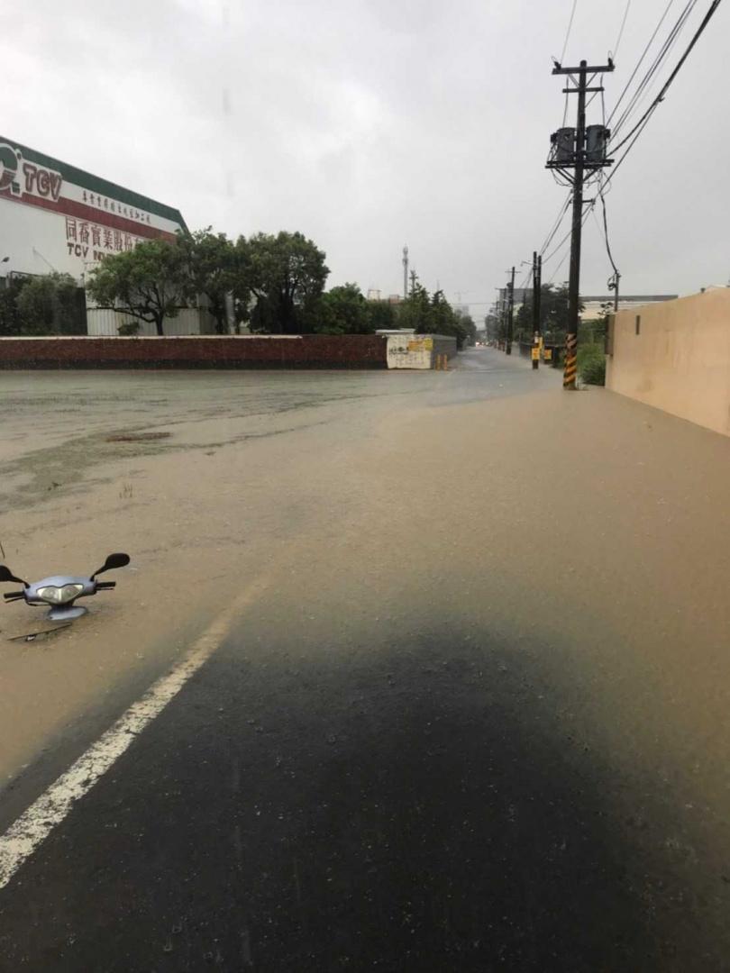 大寮地區也淹水嚴重分不清是道路還是水溝,一名騎士將機車不慎騎進低窪區動彈不得。(圖/翻攝畫面)