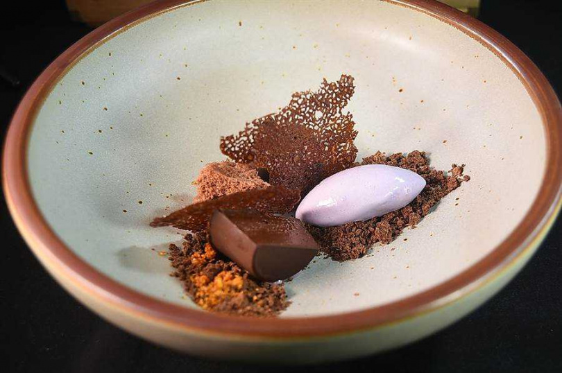James Sharman為〈 The Tavernist〉全新套餐設計的甜點〈巧克力.紫羅蘭〉,是用煙燻巧克力凍糕、巧克力土壤、巧克力微波蛋糕,以及 蜂蜜椪糖搭配 紫羅蘭酸奶冰淇淋。(圖/姚舜)