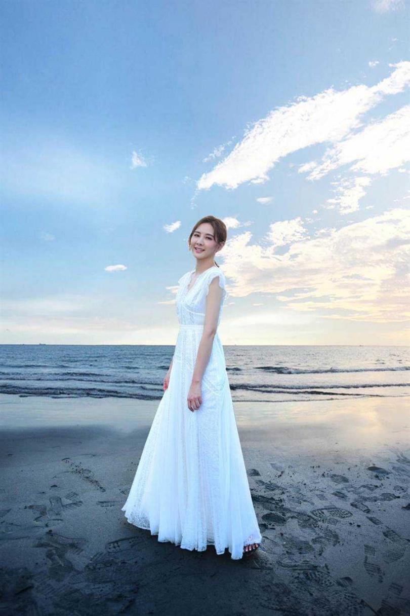 安心亞身著白色洋裝漫步在漁光島沙灘。(圖/環球音樂提供)