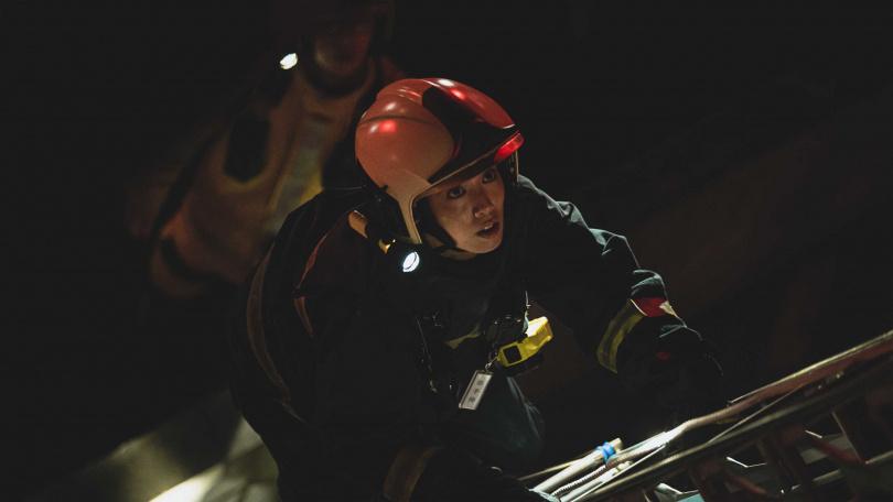 陳庭妮著消防衣驚險攀爬三層樓高的關東梯救援。(圖/公視)