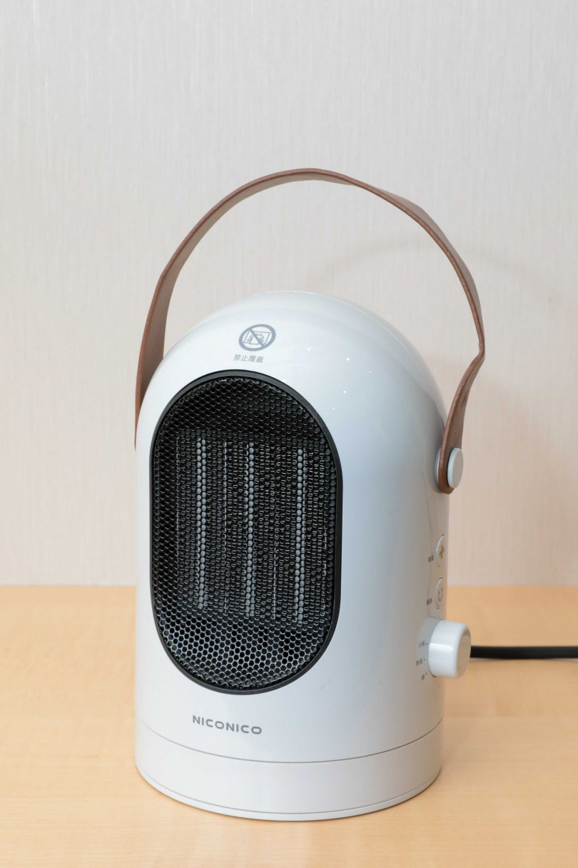 小型陶瓷電暖器適合放在桌上或腳邊使用。圖為NICONICO NI-EH809冷暖兩用電暖器,附有提把,售價1,280元。(圖/馬景平攝)