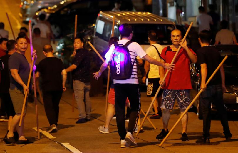 5日晚間突出現大批手持木棍的男子追打示威者。(圖/翻攝自路透社)
