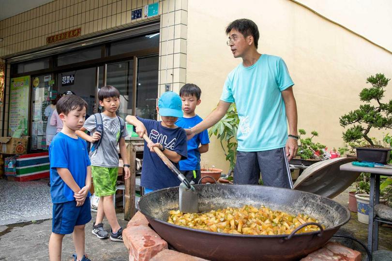 「點心城冬瓜茶」的老闆在店門前熱情講解製作冬瓜茶的方法,並協助小朋友親自體驗炒冬瓜糖。(圖/宋岱融攝)