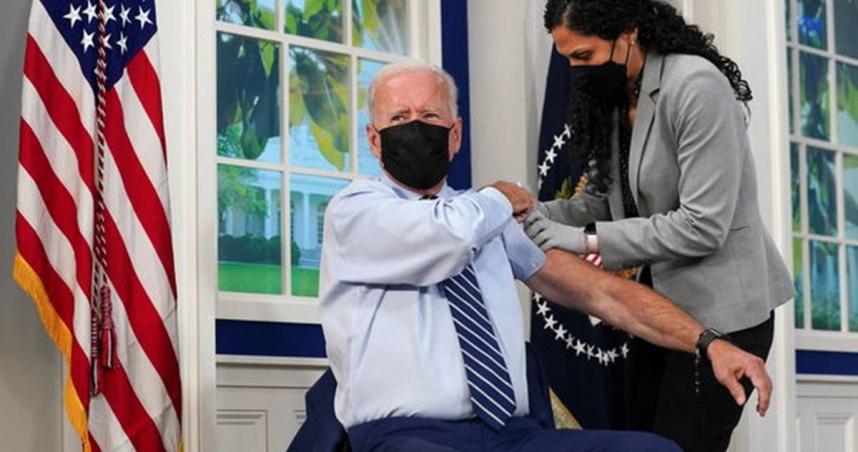 美國總統拜登(Joe Biden)在美國華盛頓白宮,示範捲起袖子接受第三劑疫苗接種。(圖/路透)